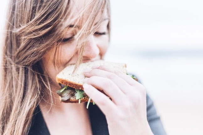 Woman eating bread which can affect insulin resistance